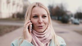 Mujer caucásica de la cámara lenta que habla en el teléfono Sonrisa de charla del blonde hermoso elegante precioso de los jóvenes almacen de metraje de vídeo