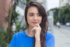 Mujer caucásica de pensamiento con la camisa azul en ciudad Foto de archivo