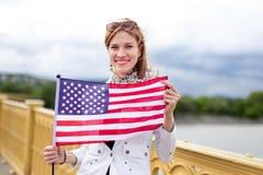 Mujer caucásica del patriota joven con la sonrisa dentuda que estira la bandera de los E.E.U.U. fotos de archivo