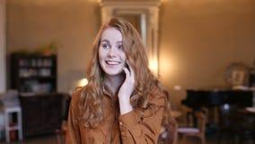 Mujer caucásica del pelo rojo joven feliz que habla en el teléfono celular en café almacen de metraje de vídeo