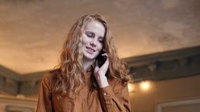 Mujer caucásica del pelo rojo joven que habla seriamente en el teléfono celular en café almacen de metraje de vídeo