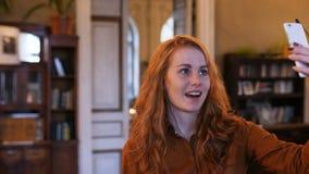 Mujer caucásica del pelo rojo joven que toma Selfie en café almacen de metraje de vídeo