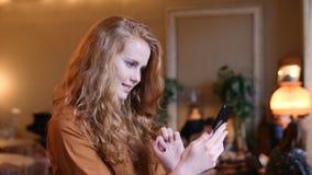 Mujer caucásica del pelo rojo joven usando tecnología elegante del teléfono en café almacen de metraje de vídeo