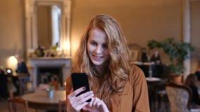 Mujer caucásica del pelo rojo joven usando tecnología elegante del teléfono en café metrajes