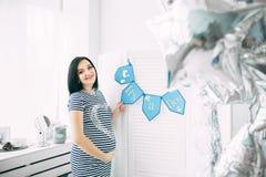 Mujer caucásica embarazada hermosa feliz con el vientre grande en vestido en la habitación del niño con los globos, parrents futu imágenes de archivo libres de regalías