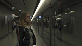 Mujer caucásica en el tren que espera de la estación de metro en la plataforma Mujer joven del viajero en metro Muchacha en moder almacen de metraje de vídeo
