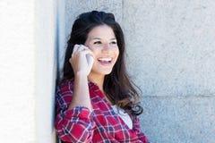 Mujer caucásica en ropa casual que se ríe del teléfono Imagen de archivo