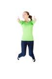Mujer caucásica feliz joven que salta en el aire con los pulgares para arriba Imágenes de archivo libres de regalías