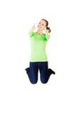 Mujer caucásica feliz joven que salta en el aire con los pulgares para arriba Fotos de archivo