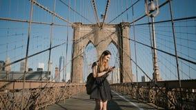 Mujer caucásica feliz joven que usa smartphone en el puente de Brooklyn, Nueva York La empresaria femenina utiliza app que hace c metrajes