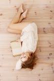 Mujer caucásica feliz que miente en el piso y que lee un libro. Fotos de archivo libres de regalías