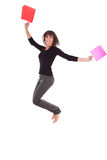 Mujer caucásica feliz que salta con los bolsos de compras Foto de archivo