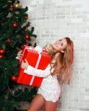 Mujer caucásica feliz rubia con el regalo rojo cerca del árbol de navidad Imágenes de archivo libres de regalías