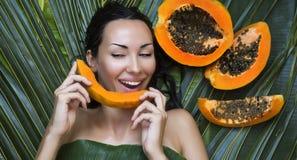Mujer caucásica hermosa con la papaya de la fruta fresca al aire libre Él fotos de archivo libres de regalías