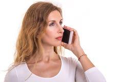 Mujer caucásica hermosa en la camiseta blanca usando smartphone stu fotografía de archivo libre de regalías