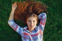Mujer caucásica hermosa joven con el pelo rojo que miente en hierba en camisa de tela escocesa Fotos de archivo libres de regalías