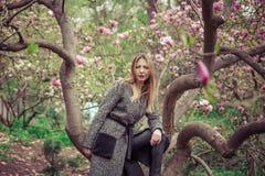 Mujer caucásica hermosa joven en el jardín floreciente de la primavera de magnolias La muchacha en el jardín en un día nublado Fotos de archivo