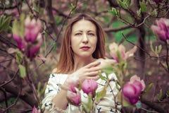 Mujer caucásica hermosa joven en el jardín floreciente de la primavera de magnolias La muchacha en el jardín en un día nublado Imagen de archivo libre de regalías
