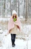 Mujer caucásica hermosa joven en la ropa y el gigante del invierno que hacen punto la manta del rosa en colores pastel imagen de archivo libre de regalías