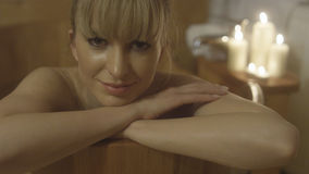 Mujer caucásica hermosa joven que toma el baño en una tina de madera Fotos de archivo libres de regalías