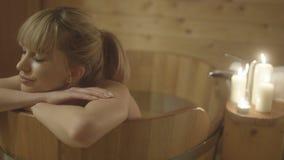 Mujer caucásica hermosa joven que toma el baño en una tina de madera Imagenes de archivo