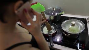 Mujer caucásica hermosa que habla en el teléfono mientras que cocina almacen de metraje de vídeo