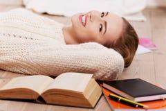 Mujer caucásica hermosa que miente en el piso con los libros. Fotografía de archivo