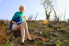 Mujer caucásica joven asentada en paisaje estéril Imágenes de archivo libres de regalías