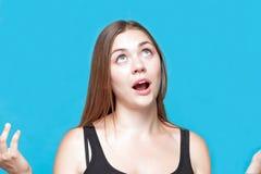 Mujer caucásica joven atractiva con la rogación de las actitudes del pelo oscuro, hahds y ojos azules para arriba, boca abierta E foto de archivo libre de regalías