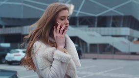 Mujer caucásica joven atractiva que sale del coche lujoso, hablando por el teléfono Mirada de moda, pelo rizado metrajes