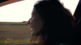 Mujer caucásica joven bonita en el coche y la mano que juegan en el aire en los rayos de la puesta del sol metrajes