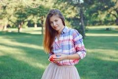 mujer caucásica joven con el pelo rojo largo en la camisa de tela escocesa que presenta en parque Fotografía de archivo libre de regalías