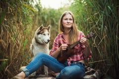 Mujer caucásica joven con el perro que juega el ukelele foto de archivo