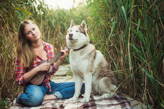 Mujer caucásica joven con el perro que juega el ukelele foto de archivo libre de regalías