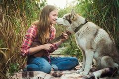 Mujer caucásica joven con el perro que juega el ukelele imagenes de archivo