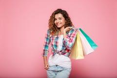 Mujer caucásica joven con hacer compras de los bolsos aislado Imagen de archivo