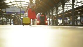Mujer caucásica joven con la maleta que corre para coger el tren adentro antes de que deje la estación sin ella almacen de video