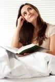 Mujer caucásica joven de la dicha que se sienta en cama Imágenes de archivo libres de regalías