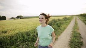 Mujer caucásica joven de la muchacha que disfruta de vida y que corre activar en camino español del campo a través de campo de tr almacen de metraje de vídeo