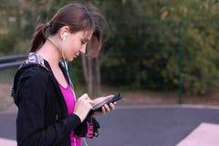 Mujer caucásica joven en cintas casuales de la ropa de deportes en el teléfono móvil que permanece en la tierra de deporte verde  imágenes de archivo libres de regalías