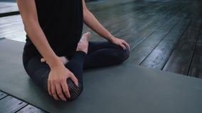 Mujer caucásica joven en el mono que se relaja practicando la yoga Padmasana Primer de las manos, pies en la posición de loto Chi almacen de metraje de vídeo