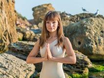 Mujer caucásica joven en el mono que se relaja practicando yoga en la playa cerca del mar tranquilo, primer de manos, mudra gyan imagenes de archivo