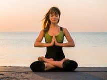 Mujer caucásica joven en el mono que se relaja practicando yoga en la playa cerca del mar tranquilo, primer de manos, mudra gyan foto de archivo libre de regalías