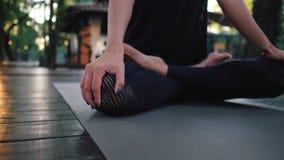 Mujer caucásica joven en el mono que se relaja practicando yoga Primer de las manos, pies en la posición de loto Chica metrajes