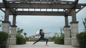 Mujer caucásica joven en la ropa de deportes que se relaja practicando yoga descalzo en el parque de la ciudad Fondo de la salida almacen de video