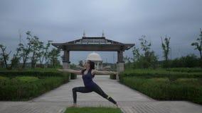 Mujer caucásica joven en la ropa de deportes que se relaja practicando yoga descalzo en el parque de la ciudad Fondo de la salida almacen de metraje de vídeo