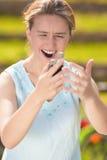 Mujer caucásica joven enojada y furiosa con el teléfono móvil en las manos Foto de archivo libre de regalías