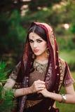 Mujer caucásica joven hermosa en sari india tradicional de la ropa con el tatuaje nupcial del maquillaje y de la joyería y de la  foto de archivo