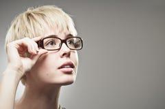 Mujer caucásica joven hermosa que ajusta sus vidrios Fotos de archivo