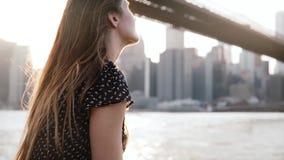 Mujer caucásica joven hermosa que se sienta en la cerca del terraplén en el puente de Brooklyn, Nueva York, disfrutando de la cám almacen de metraje de vídeo
